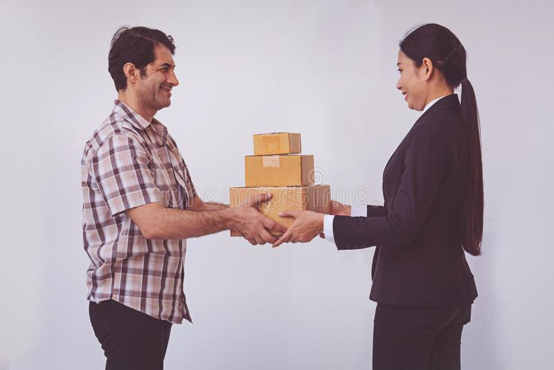 A mulher que aceita recebe uma entrega das caixas do homem do asi?tico da entrega imagens de stock
