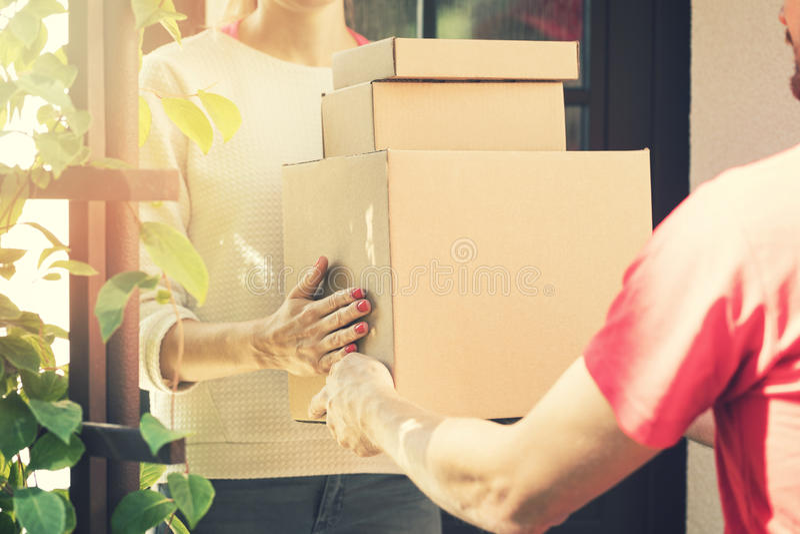 Mulher que aceita uma entrega a domicílio das caixas do entregador fotos de stock royalty free