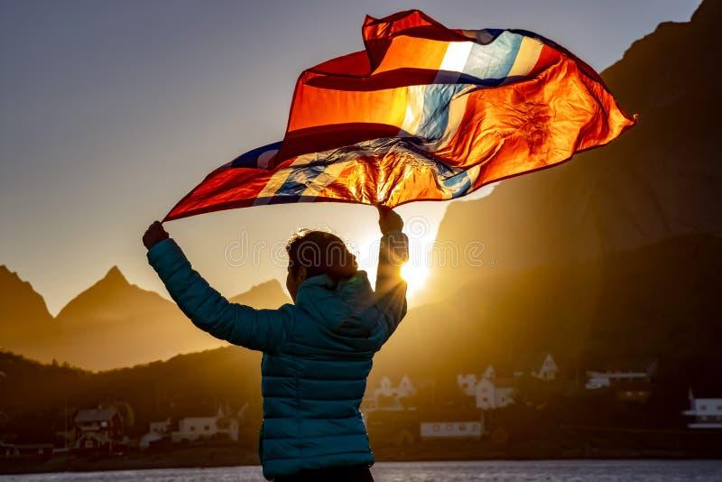 Mulher que acena a bandeira de Noruega no por do sol foto de stock