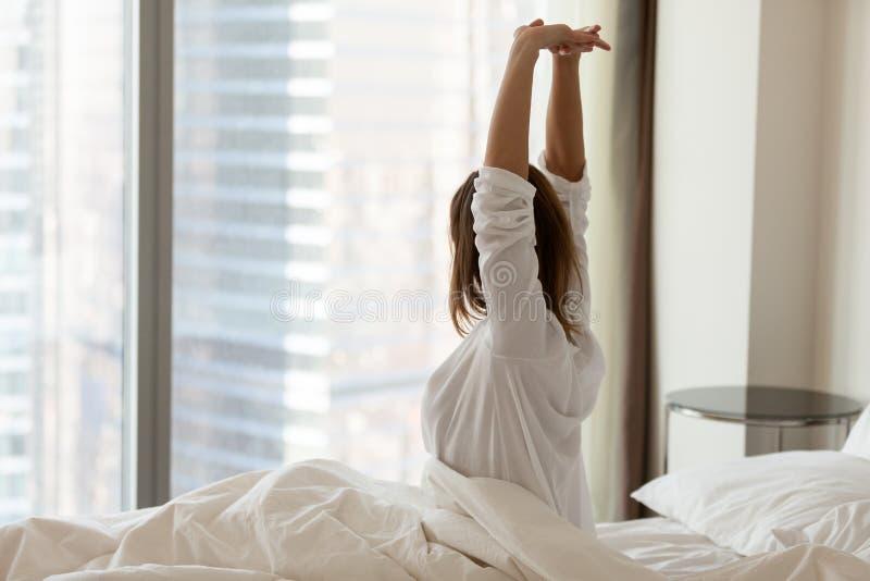 Mulher que acorda o esticão feliz na cama confortável no hotel fotografia de stock