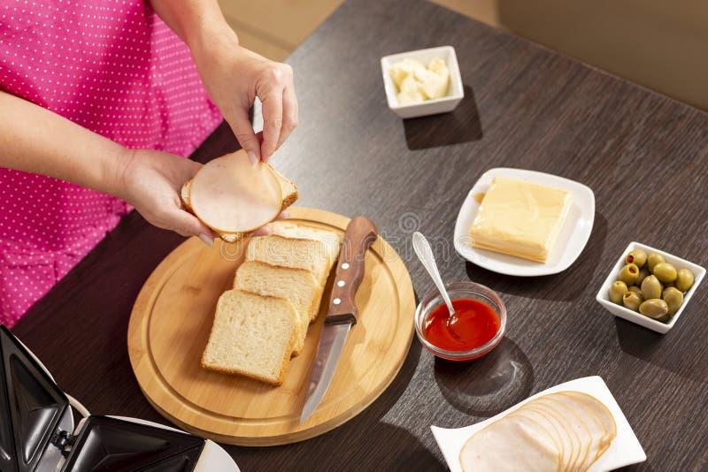 Mulher que adiciona o salame em um sanduíche imagens de stock