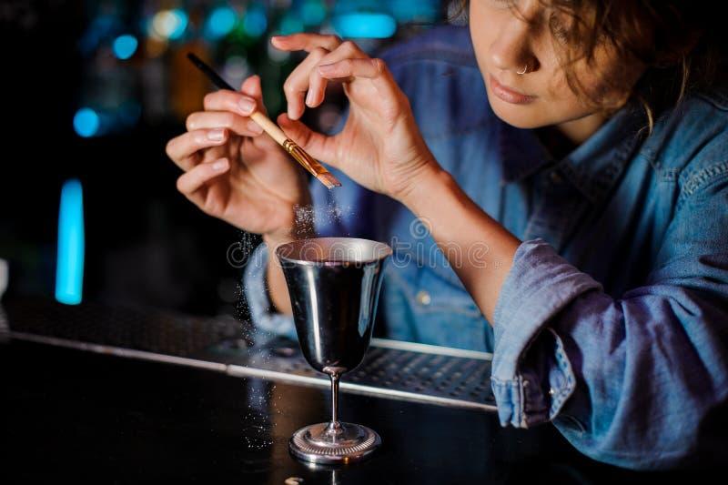 Mulher que adiciona um brilho da escova a um vidro de cocktail com bebida alcoólica fotos de stock