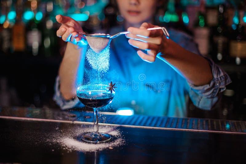 Mulher que adiciona a um cocktail marrom um pó do açúcar através do filtro na luz azul fotos de stock