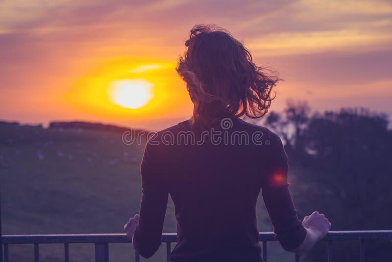 Mulher que admira o por do sol de seu balcão foto de stock