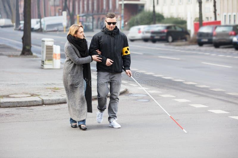Mulher que ajuda ao homem cego na rua fotografia de stock royalty free