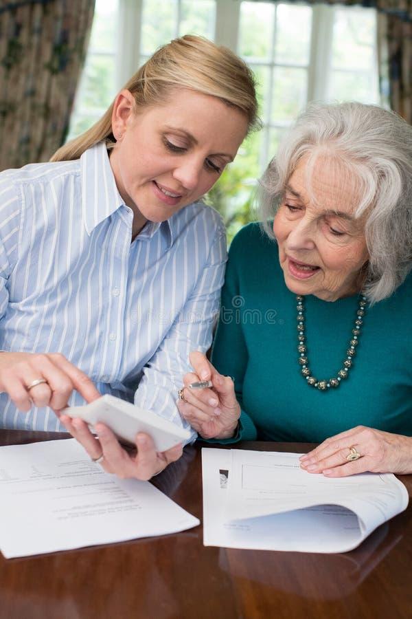Mulher que ajuda o vizinho superior com documento imagem de stock royalty free