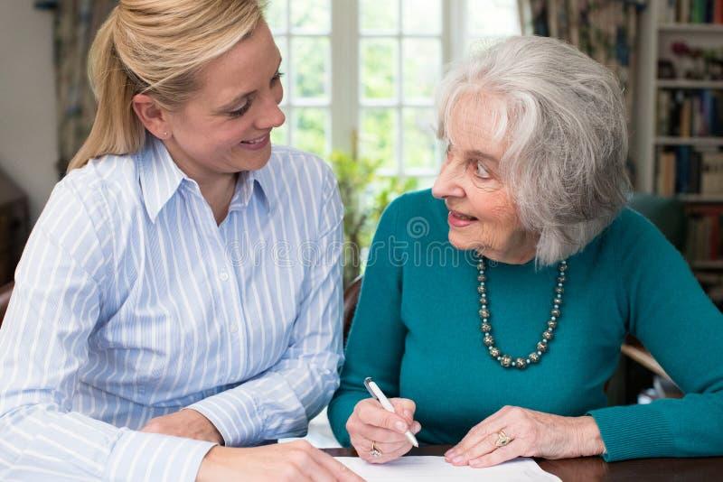 Mulher que ajuda o vizinho superior com documento imagem de stock