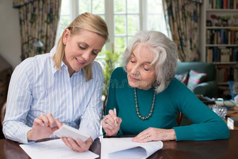 Mulher que ajuda o vizinho superior com documento imagens de stock royalty free