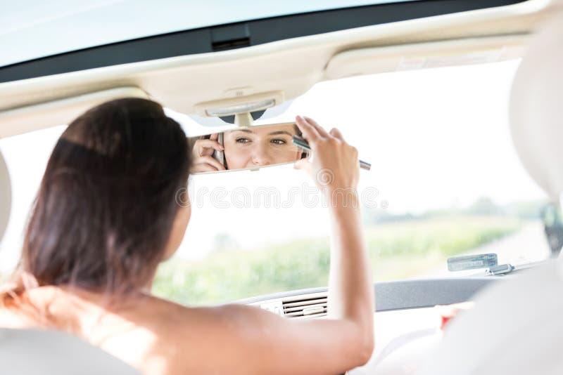 Mulher que ajusta o espelho de rearview ao usar o telefone celular no carro fotografia de stock