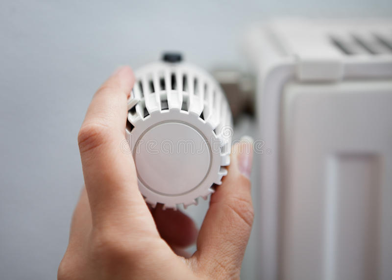 Mulher que ajusta o termostato fotografia de stock