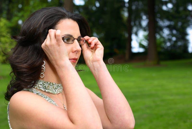 Mulher que ajusta seus vidros imagens de stock royalty free