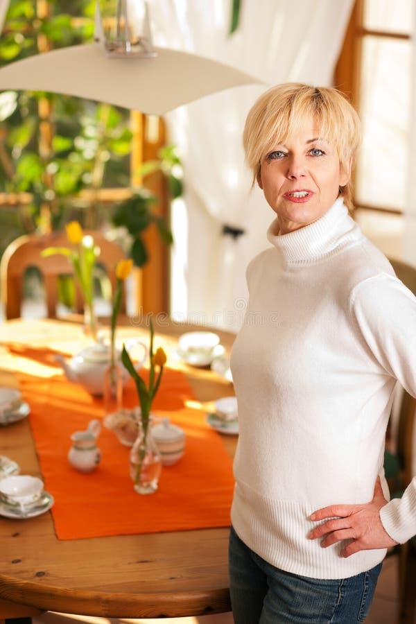 Mulher que ajusta a tabela para o chá do tempo do café fotografia de stock royalty free
