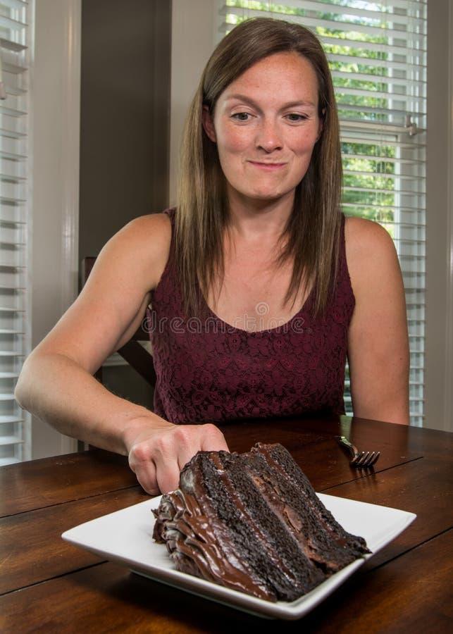 Mulher que alcança para a fatia de bolo de chocolate foto de stock
