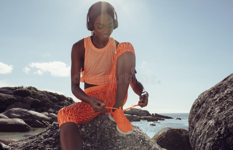 Mulher que amarra seus laços de sapata antes de uma corrida na praia fotografia de stock