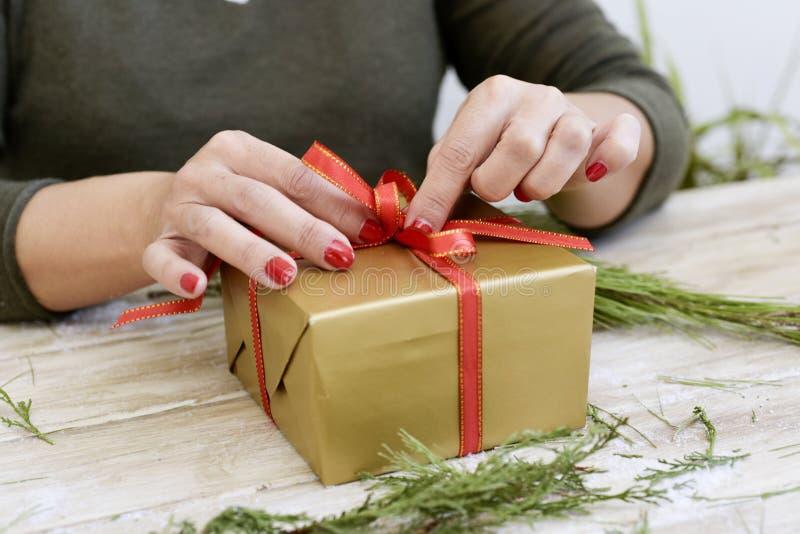 Mulher que amarra uma fita vermelha em torno de um presente fotos de stock royalty free