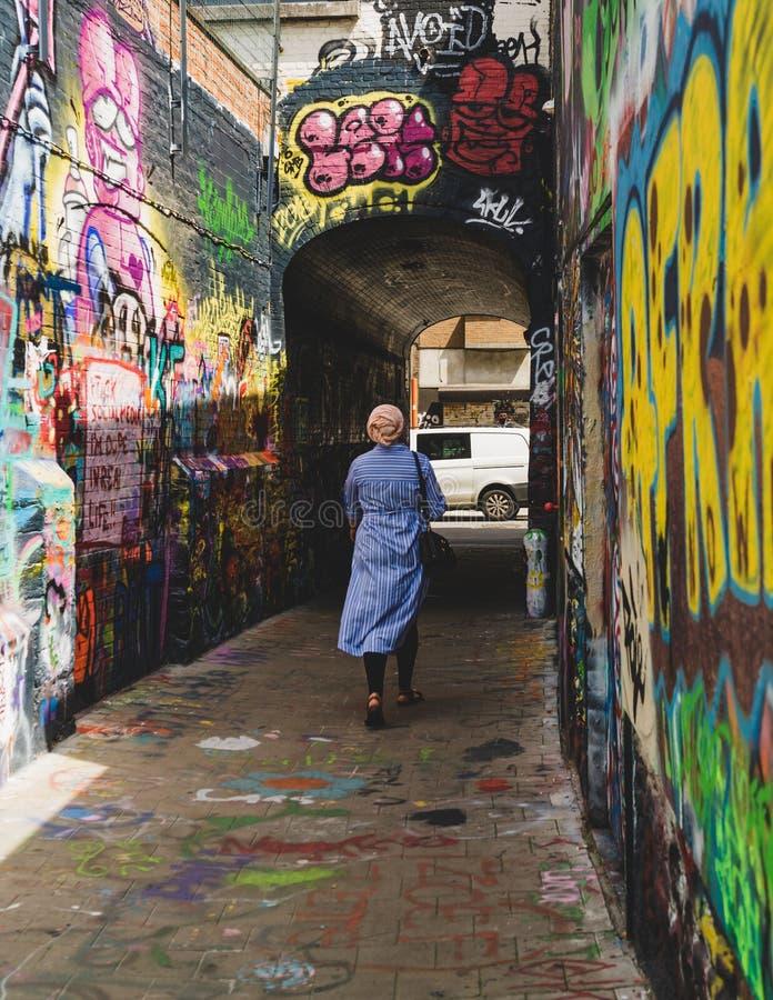 Mulher que anda abaixo da rua dos grafittis foto de stock
