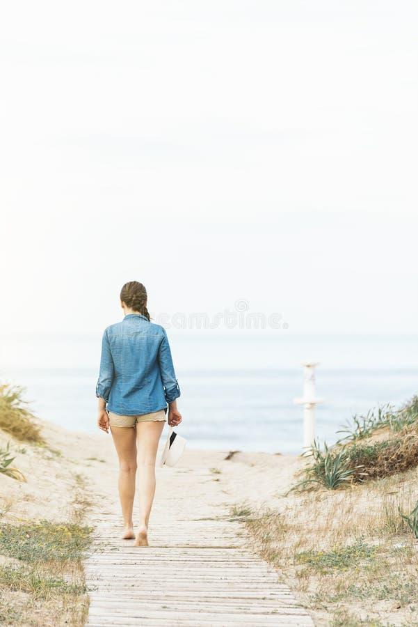Mulher que anda afastado na praia idylic fotos de stock royalty free
