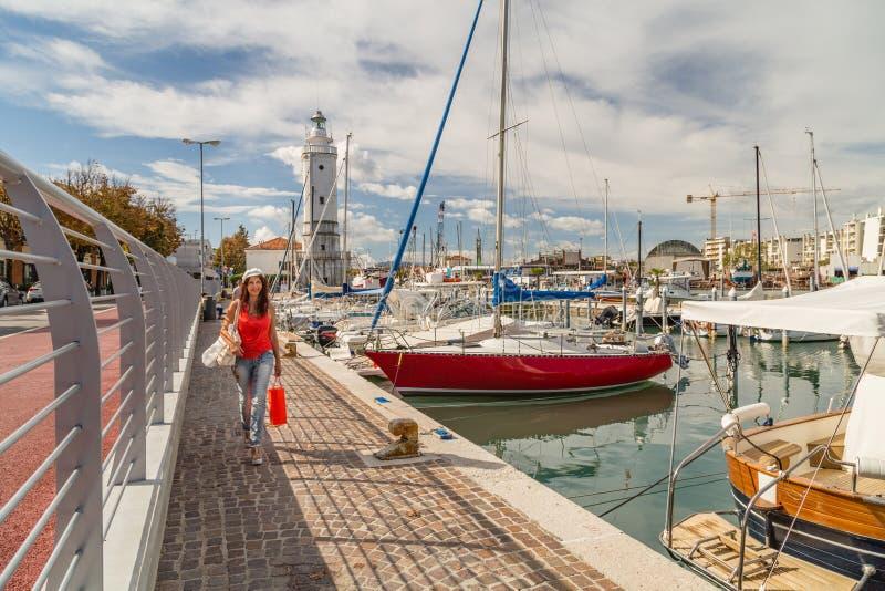 Mulher que anda ao longo do porto do canal com saco de compras foto de stock