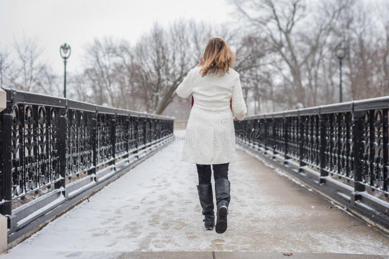 Mulher que anda através da ponte ornamentado do ferro no parque da cidade no inverno w fotografia de stock