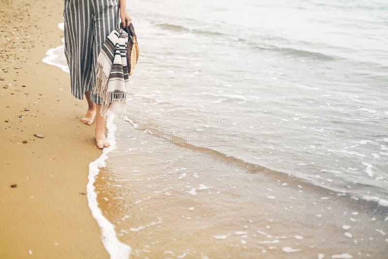 A mulher que anda com os pés descalços na praia, fecha-se acima da vista dos pés e das ondas Moça que relaxa no Sandy Beach perto fotografia de stock