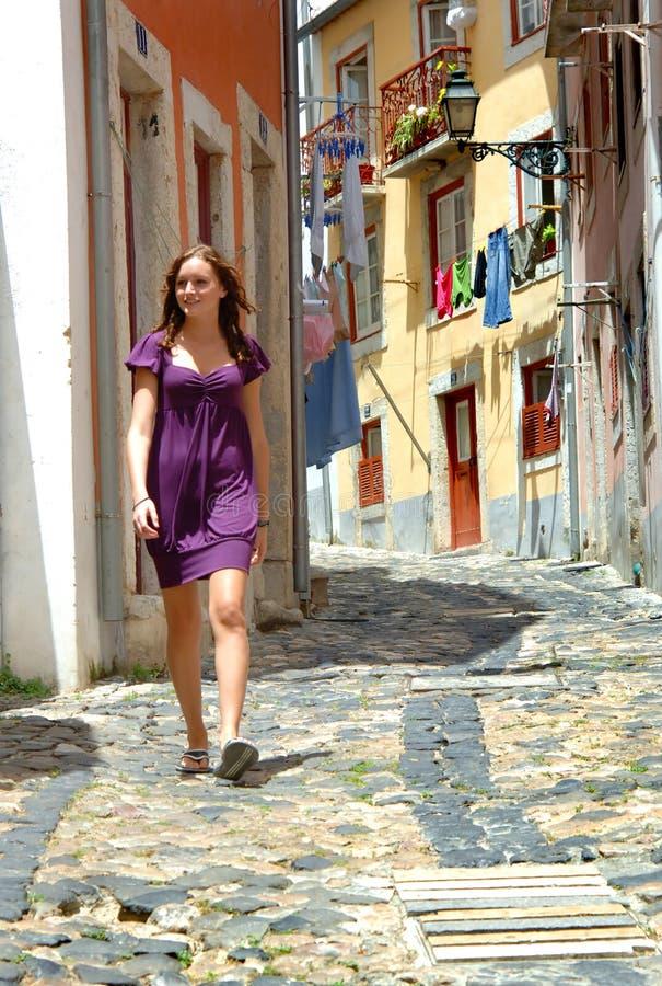 Mulher que anda em uma rua estreita de Portugal fotografia de stock