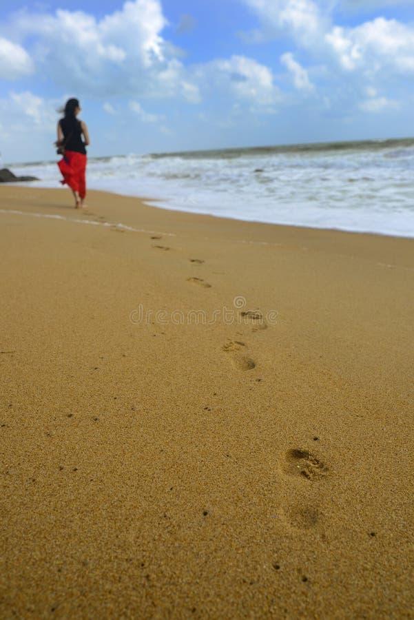 Mulher que anda na areia da praia imagem de stock