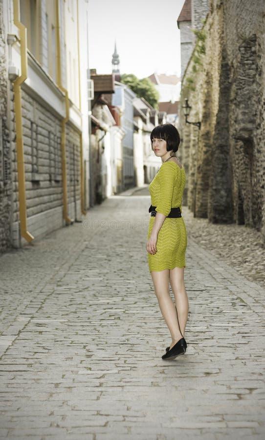 Mulher que anda na cidade velha de Tallinn fotos de stock