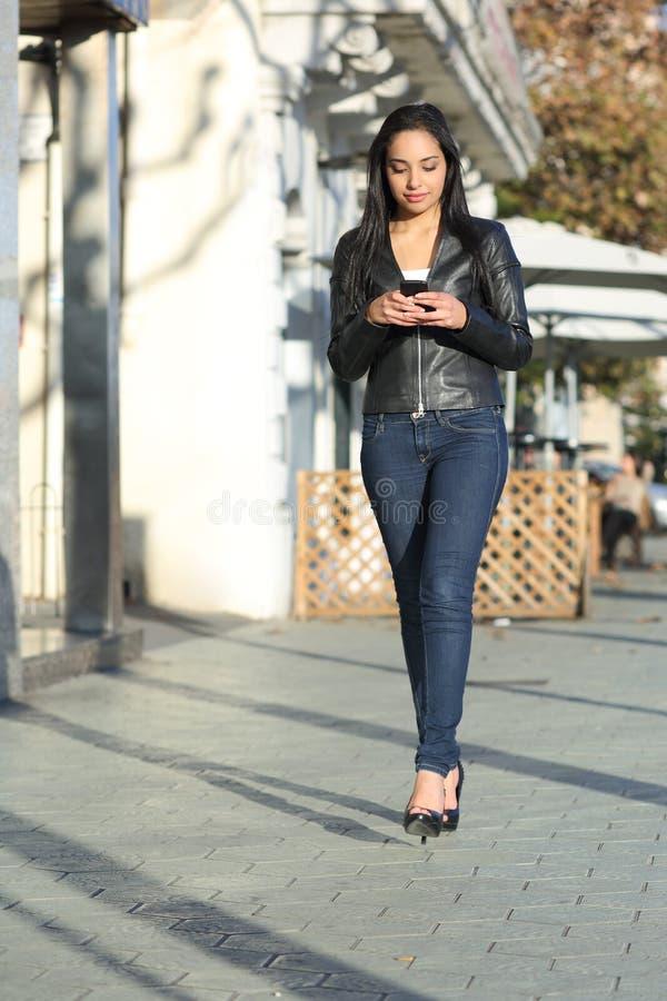 Mulher que anda na escrita da rua em um telefone esperto fotografia de stock