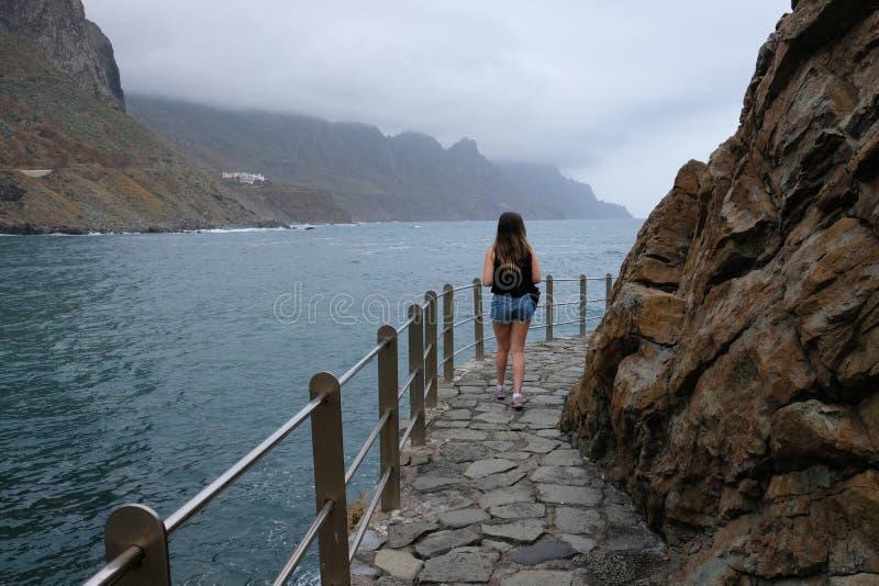 Mulher que anda na frente marítima com montanhas e o céu nebuloso no fundo imagens de stock