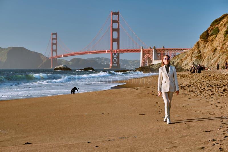 Mulher que anda na praia perto de golden gate bridge fotografia de stock