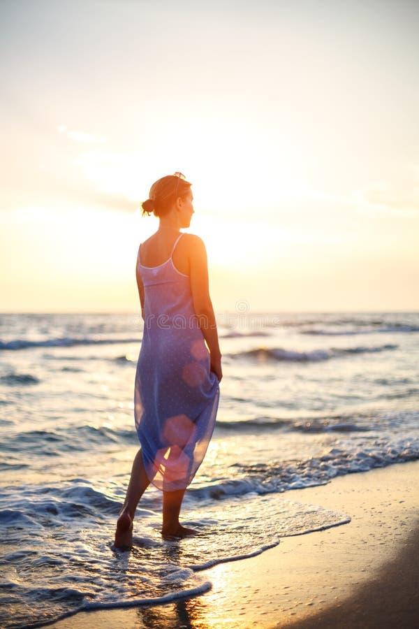 Mulher que anda na praia na ressaca no por do sol fotografia de stock royalty free