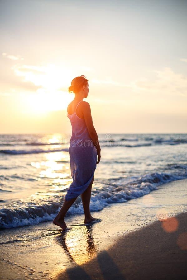 Mulher que anda na praia na ressaca no por do sol foto de stock