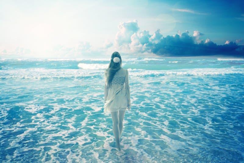 Mulher que anda na praia sonhadora que aprecia a vista para o mar fotografia de stock royalty free
