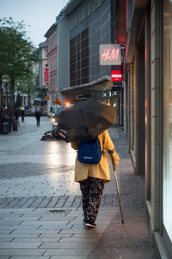 Mulher que anda na rua com o guarda-chuva na manhã no dia chuvoso fotografia de stock