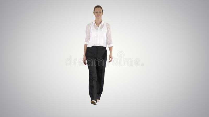 Mulher que anda no equipamento formal no fundo do inclinação foto de stock