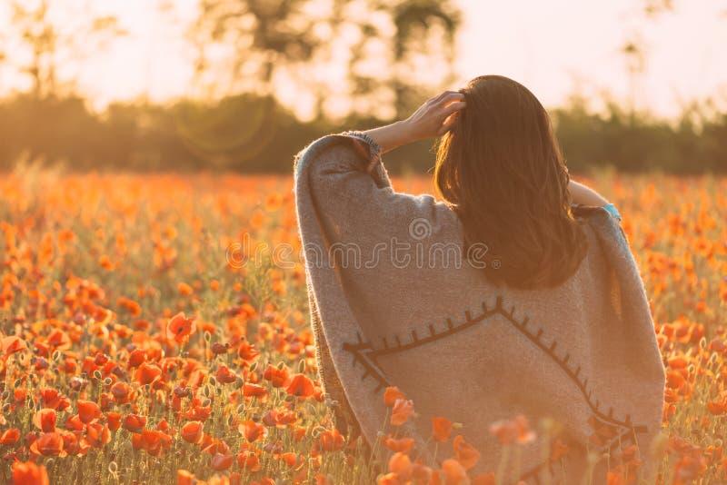 Mulher que anda no prado das papoilas na mola no por do sol imagem de stock royalty free