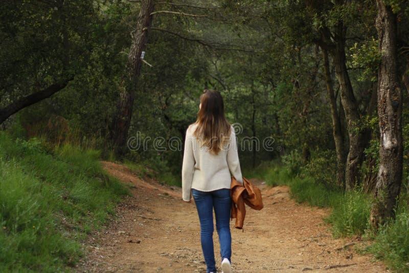 Mulher que anda no trajeto no tiro traseiro da floresta fotografia de stock