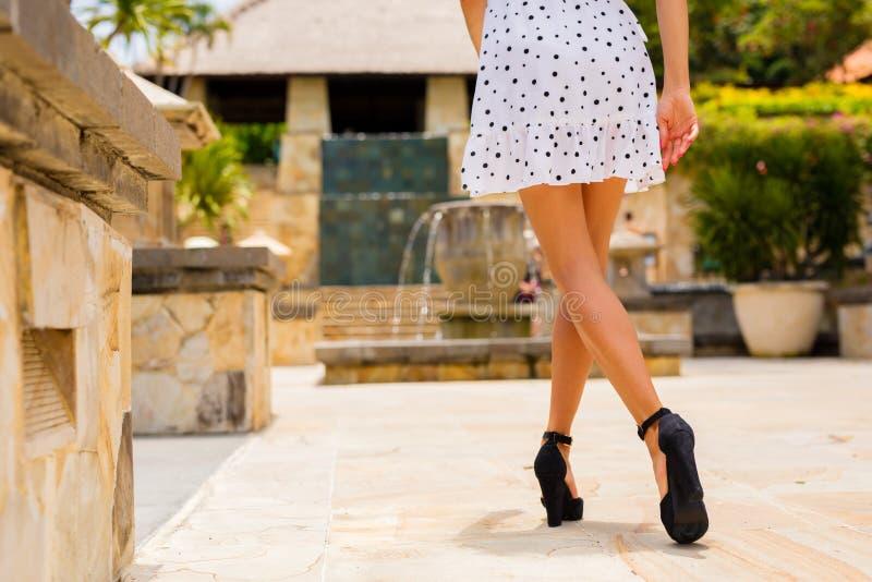Mulher que anda no vestido branco do verão e nos saltos altos pretos fotos de stock