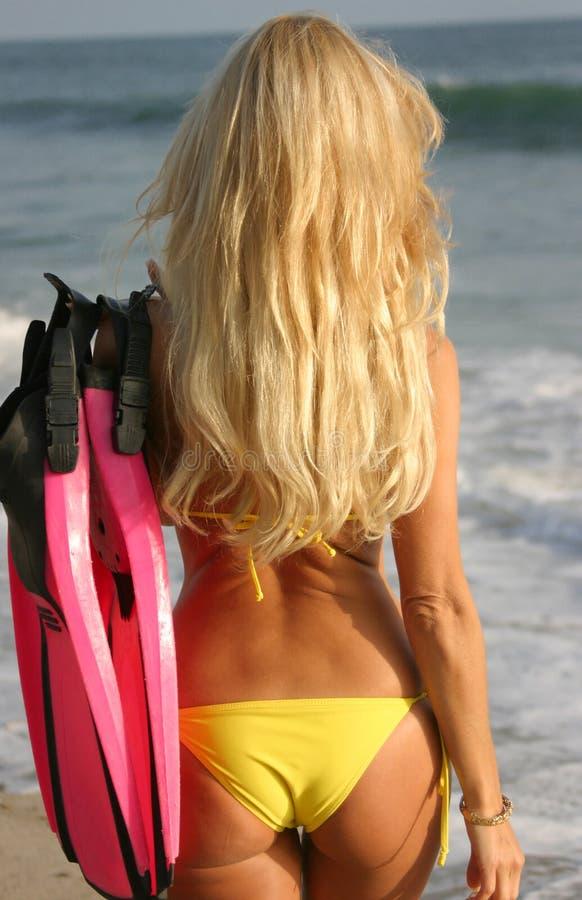 Mulher que anda para a água com aletas foto de stock