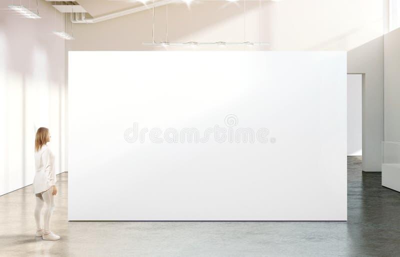 Mulher que anda perto do modelo branco vazio da parede na galeria moderna imagem de stock royalty free