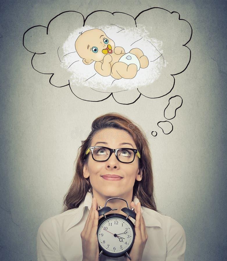 Mulher que antecipa um bebê que olha mantendo o despertador fotografia de stock