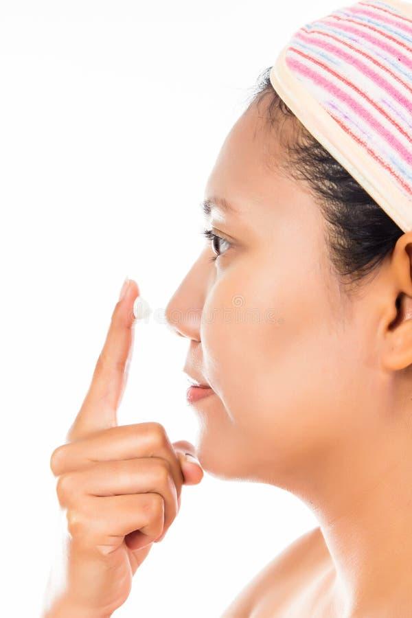 Mulher que aplica algum creme facial fotos de stock