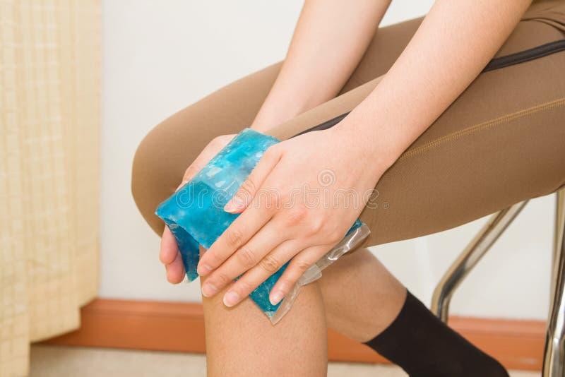 Mulher que aplica a bolsa de gelo em joelho de ferimento inchado foto de stock