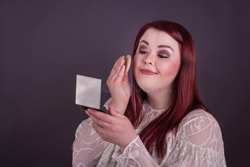 Mulher que aplica a composição que olha no espelho compacto foto de stock