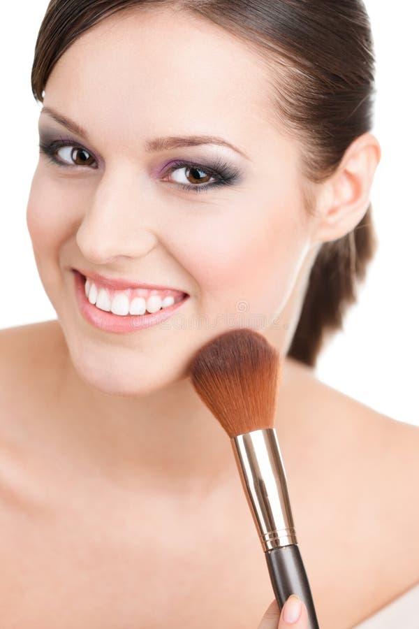 Mulher que aplica cosméticos a sua face imagem de stock royalty free