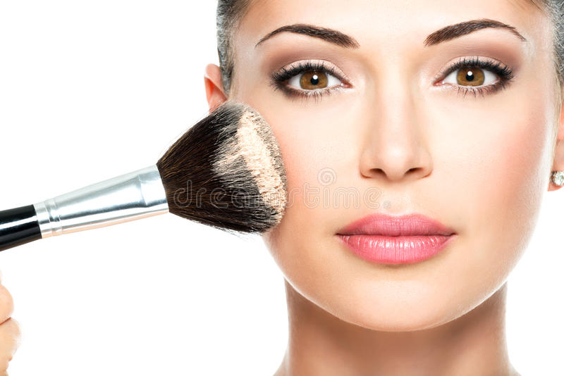 Mulher que aplica a fundação tonal cosmética seca na cara fotos de stock