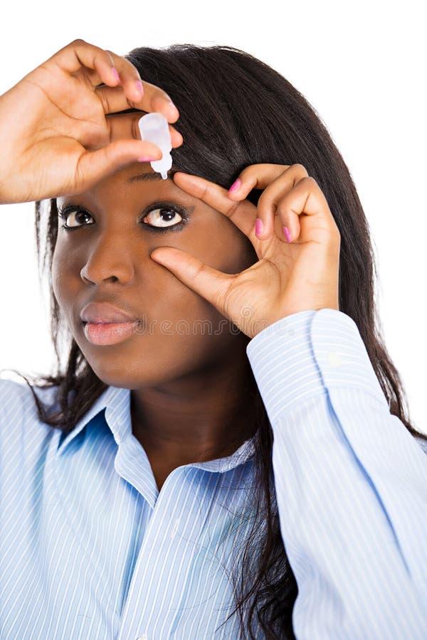 Mulher que aplica gotas de olho fotografia de stock