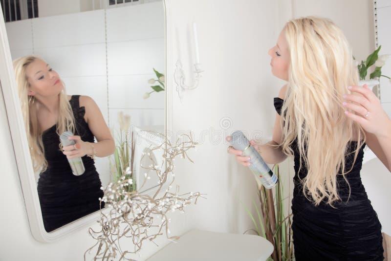 Mulher que aplica a laca a seu cabelo foto de stock royalty free