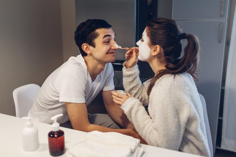 Mulher que aplica a máscara da argila na cara do seu noivo Pares de amor novos que tomam da pele em casa fotos de stock royalty free