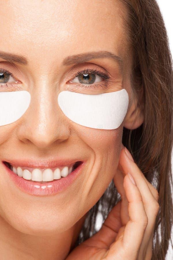 Mulher que aplica a máscara de olho do gel fotografia de stock royalty free
